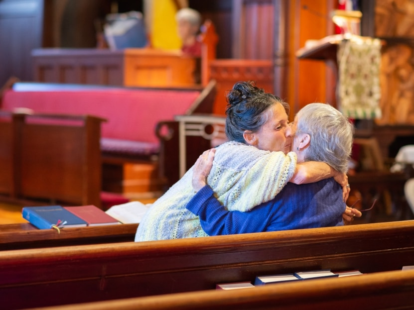 Two people hug inside St. Mary's church in Pacific Grove, California