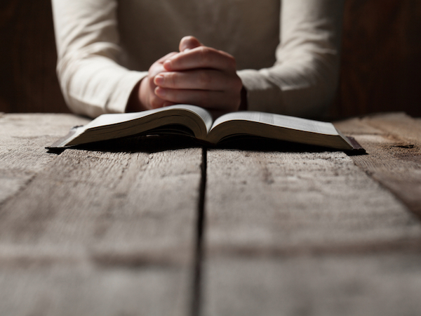 woman with hands folded in front of Bible